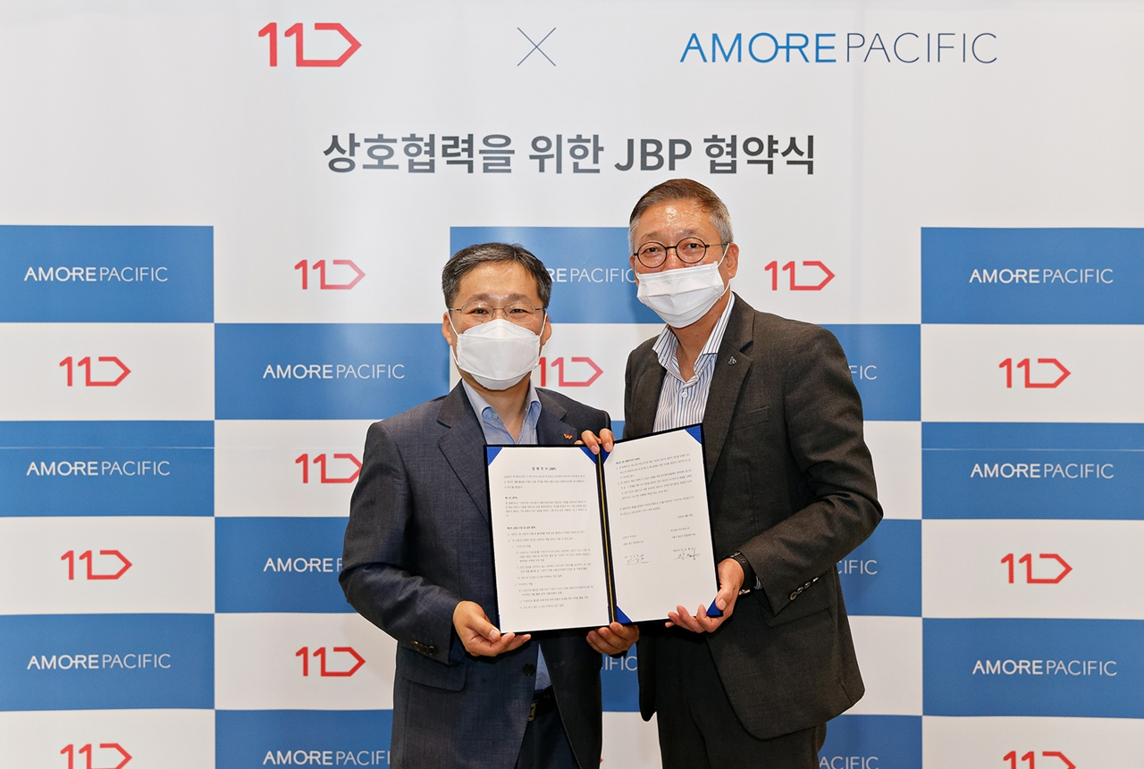 11Street CEO Lee Sang-ho (left) and Amorepacific Group CEO Ahn Se-hong pose in the joint business partnership ceremony held at Amorepacific headquarters in Seoul on Tuesday. (Amorepacific)