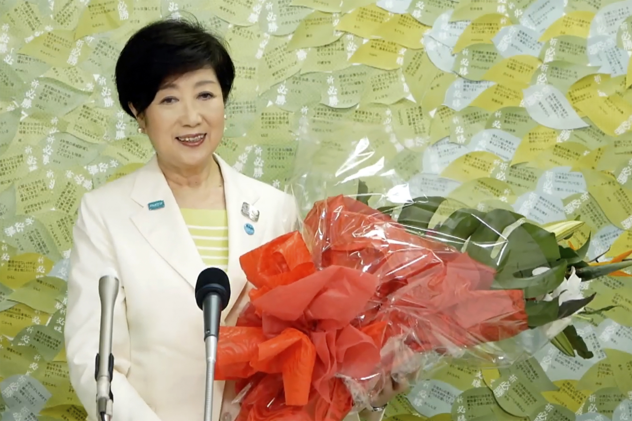 In this image made from YouTube provided by Koike Yuriko Official Channel, Tokyo Gov. Koike recieves a bunch of flower from supporter during her gubernatorial election victory press conference at her election office in Tokyo, Sunday. (AP-Yonhap)