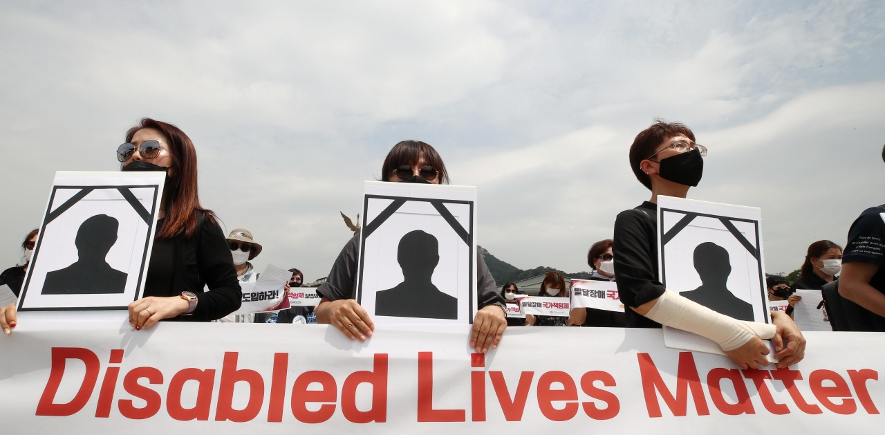 Families of people with disabilities hold a rally in front of Cheong Wa Dae in Seoul on June 10 to mourn the death of a mother and her son with developmental disorder in Gwangju and demand urgent action from the government to prevent such tradegies from repeating. (Yonhap)