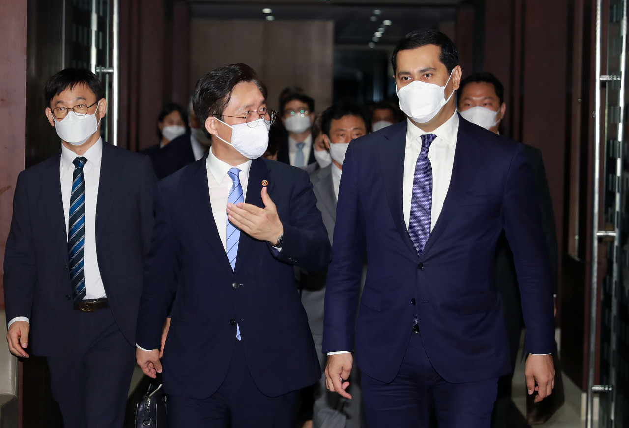 Korea's Industry Minister Sung Yun-mo (left) speaks with Uzbekistan's Deputy Prime Minister for Investments and Foreign Economic Affairs Sardor Umurzakov on their way to a bilateral meeting between the two nations held in Seoul on Monday. (Yonhap)
