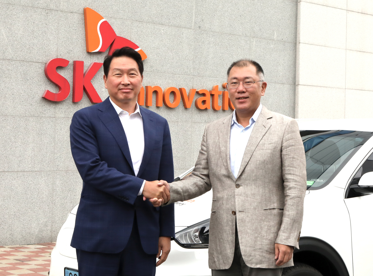 Hyundai Motor Group Executive Vice Chairman Chung Euisun (right) shakes hands with SK Group Chairman Chey Tae-won at SK Innovation's electric vehicle battery plant in Seosan, South Chungcheong Province, Tuesday. (SK Group)