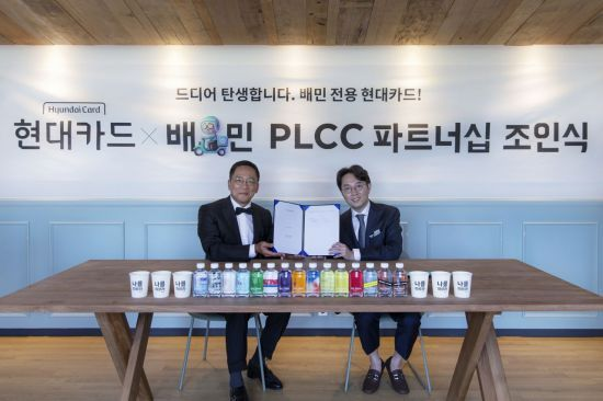 Hyundai Card CEO Ted Chung (left) and Kim Beom-joon, CEO of Woowa Brothers, participate in an event to sign a partnership on Tuesday in Seoul. (Hyundai Card)