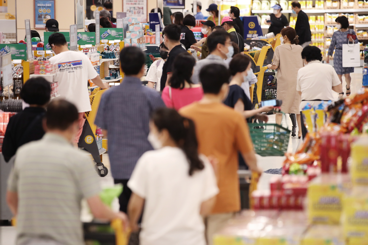 South Korean consumers shop at a local retailer in Seoul on Sunday. (Yonhap)