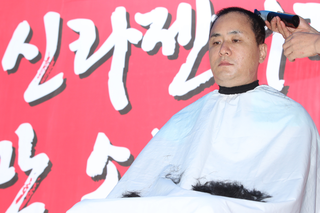 A SillaJen stock investor shaves hair in show of protest, urging the Korea Exchange to resume SillaJen's trading on the stock bourse in front of Korea Exchange's Seoul office Friday. (Yonhap)