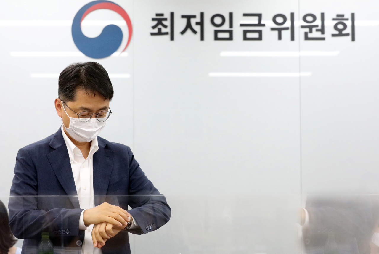 Minimum Wage Commission Chairman Park Joon-sik checks time before a general meeting of 27 members on Friday. Labor and business representatives have failed to narrow down their differences on next year`s minimum wage level even though only a few days are left to reach a final decision. (Yonhap)