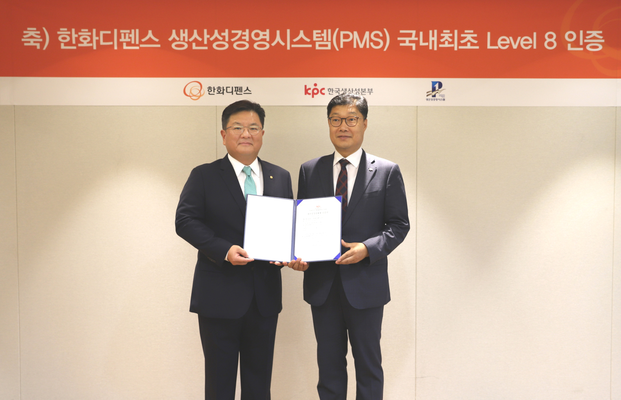 Hanwha Defense CEO Lee Sung-soo (left) accepts the company's level 8 certification from Lee Jin-hwan, head of the Korea Productivity Center's Productivity Innovation Institute. (Hanwha Defense)