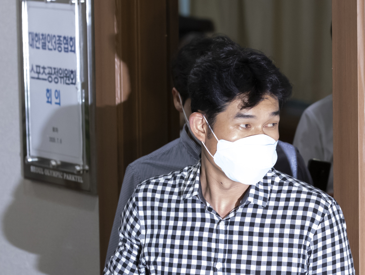 Kim Gyu-bong, head coach of the triathlon team at Gyeongju City Hall and a central figure in an abuse scandal involving a late athlete, leaves the disciplinary committee meeting held by the Korea Triathlon Federation in Seoul, July 6. (Yonhap)