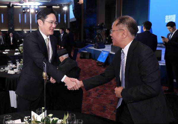 Samsung heir Lee Jae-yong (left) shakes hands with Hyundai Motor Group heir Chung Euisun during a luncheon in January. (Yonhap)