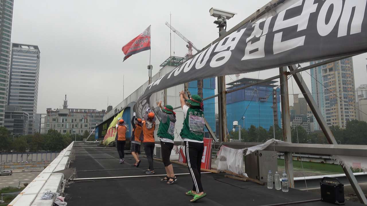 """Laid-off toll collectors perform synchronized dance movements as they protest on top of Seoul Tollgate in a scene from documentary film """"Bora Bora."""" (Kim Do-joon)"""
