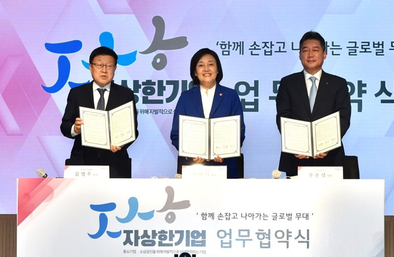 KITA Chairman Kim Young-ju (first from left), Startups Minister Park Young-sun (center) and LG International CEO Yoon Chun-sung pose for a photo after sigining an agreement to support SMEs in Seoul on Wednesday. (KITA)