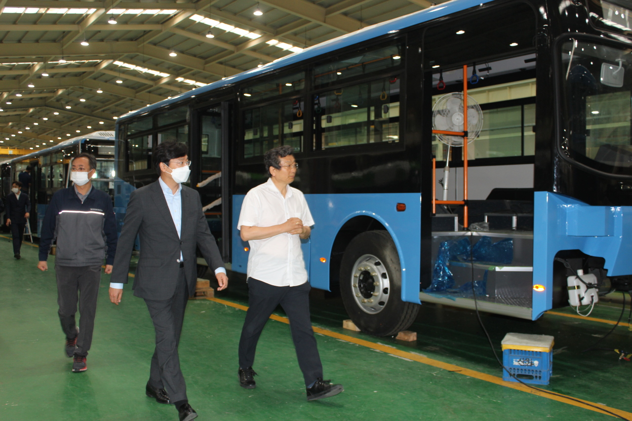 KT's connected car business head Choi Kang-rim (center) listens to Edison Motors CEO Kang Young-kwon (right) about the manufacturing process for electric buses. (KT)