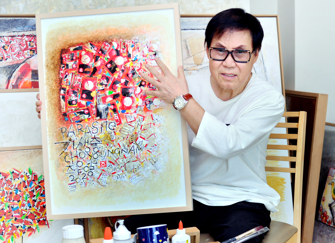 Singer-artist Cho Young-nam holds up a painting in his hwatu series during an interview with The Korea Herald on July 13. (Park Hyun-ku/The Korea Herald)