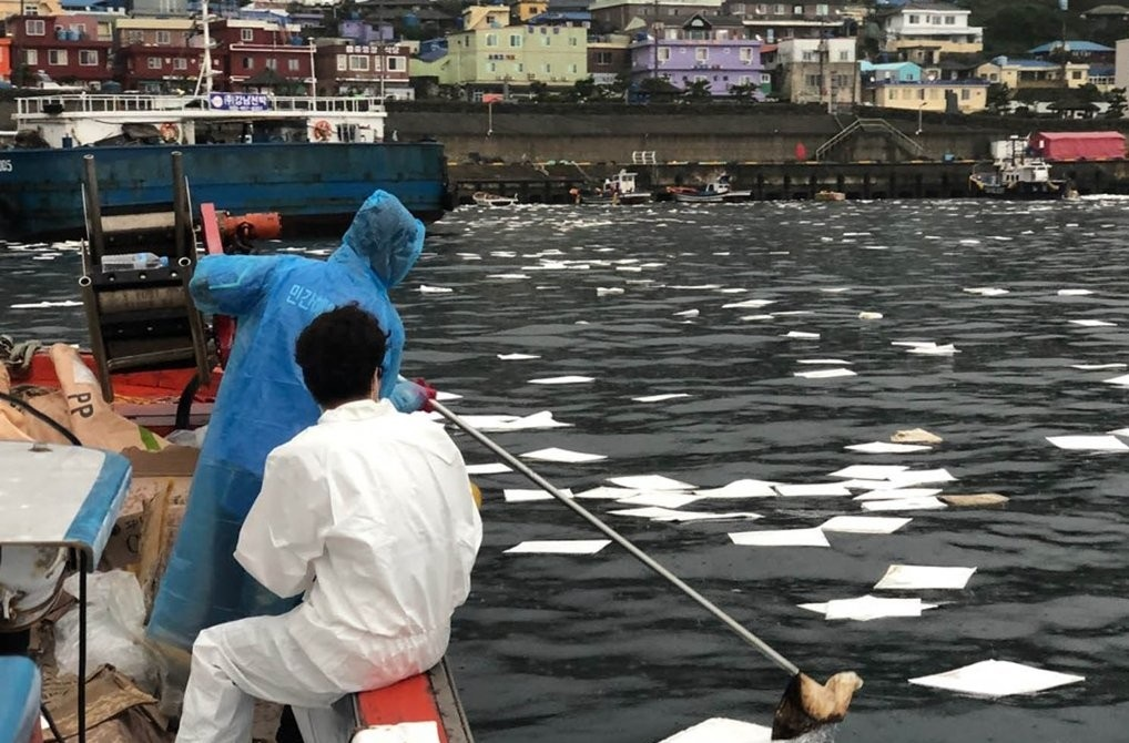 Coast Guard officials clean up spilt oil at a port on the southwestern island of Gageo, South Jeolla Province, on July 23, 2020, in this photo provided by the Mokpo office of the Korea Coast Guard. The oil spill occurred after a 78-ton tugboat at the site crashed into a 800-ton barge two days earlier. (Yonhap)