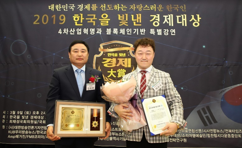 Cryptocurrency Rebalancing CEO Baek Chun-soo (right) poses after receiving a best entrepreneurship award last year. (Cryptocurrency Rebalancing)