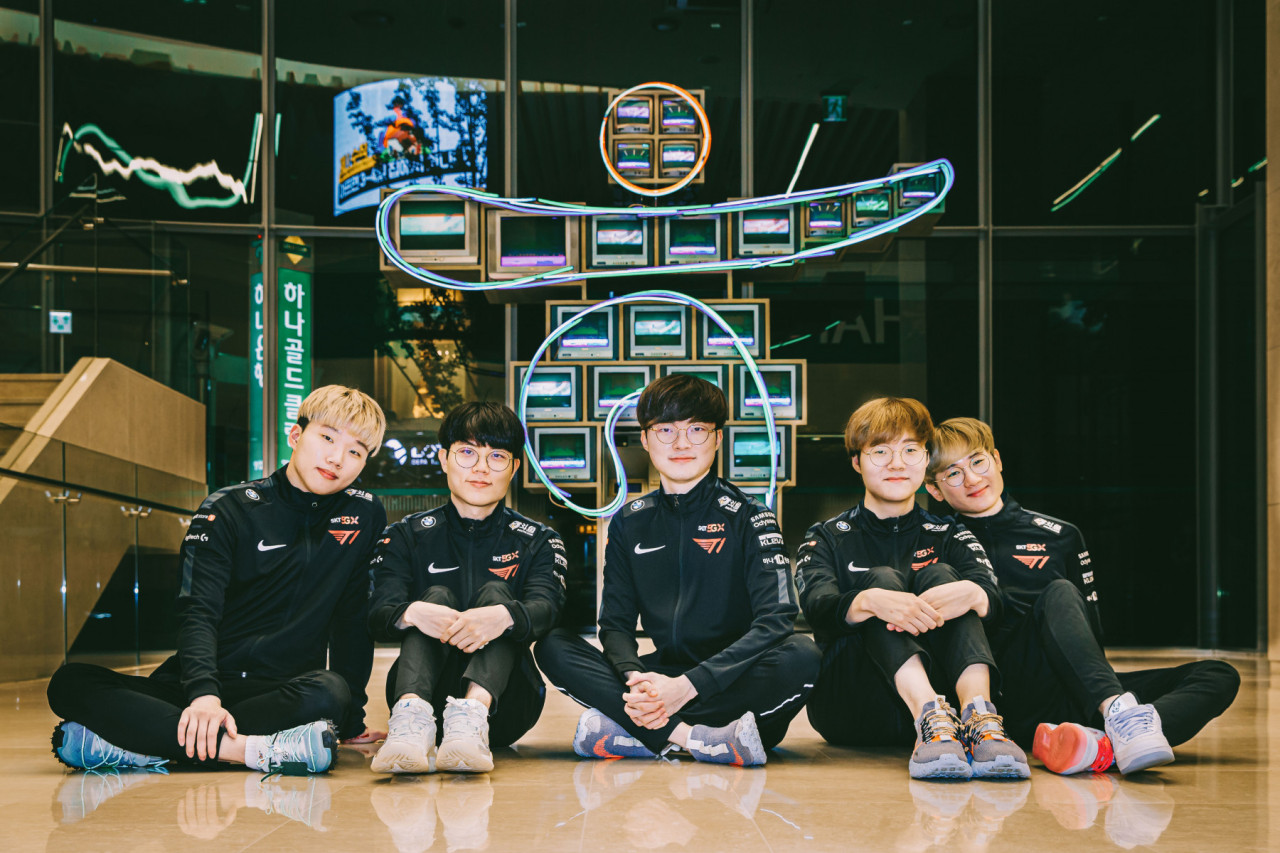 Members of T1, including Faker (center), pose in front of the Hana Bank logo after inking a sponsorship agreement. (T1)