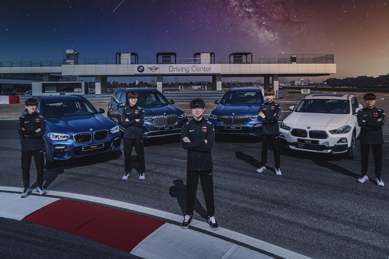 Members of T1, including Faker (center), pose in front of BMW vehicles. (T1)