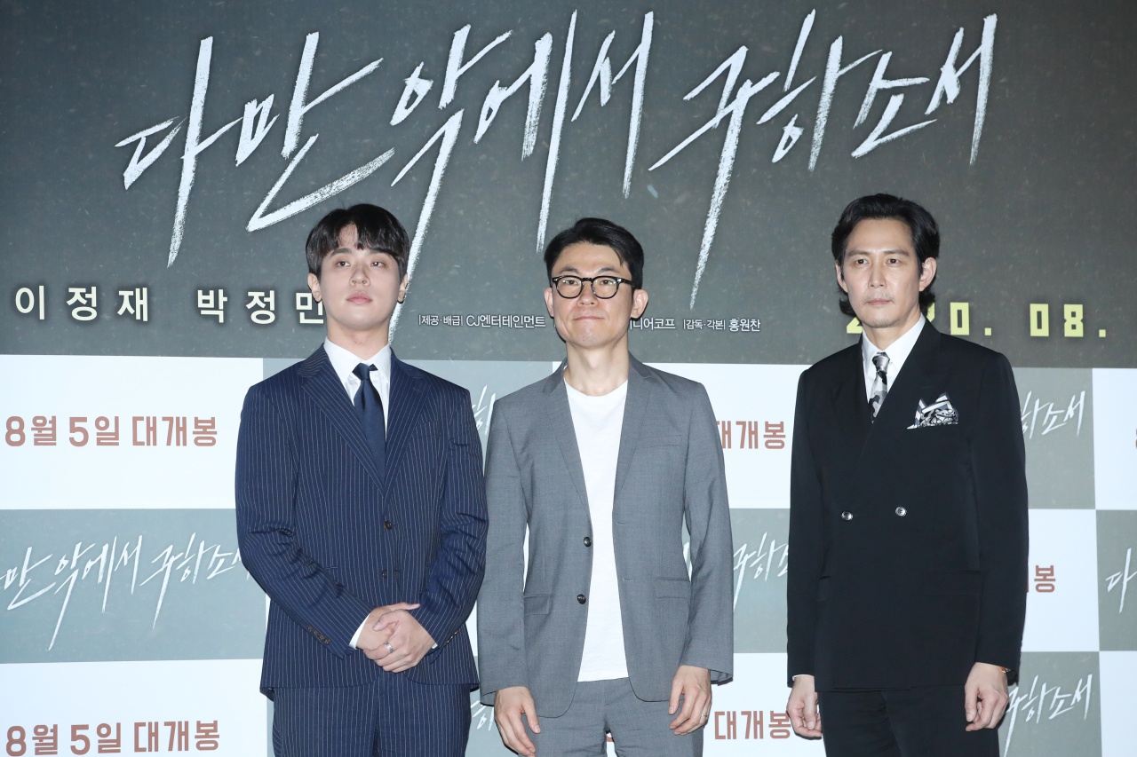 """Director Hong Won-chan (center) and lead cast members Park Jung-min (far left) and Lee Jung-jae pose at a press premiere event at CGV Yongsan I'Park Mall in Seoul on Tuesday to promote """"Deliver Us From Evil."""" (Yonhap)"""