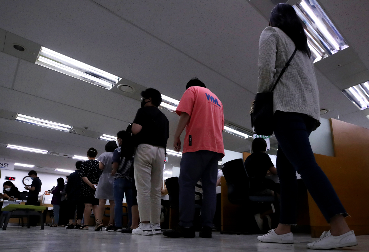 Visitors to a regional office of the Ministry of Employment and Labor in Seoul wait in line to apply for unemployment benefits earlier this year. (Yonhap)