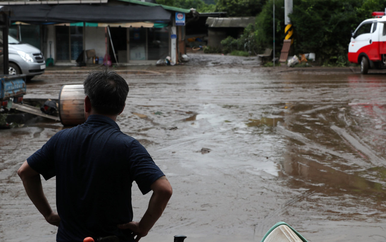 A man in Cheorwon County, Gangwon Province, stares at his village`s flooded road Monday after more than 300 millimeters of rain poured in the region overnight. (Yonhap)
