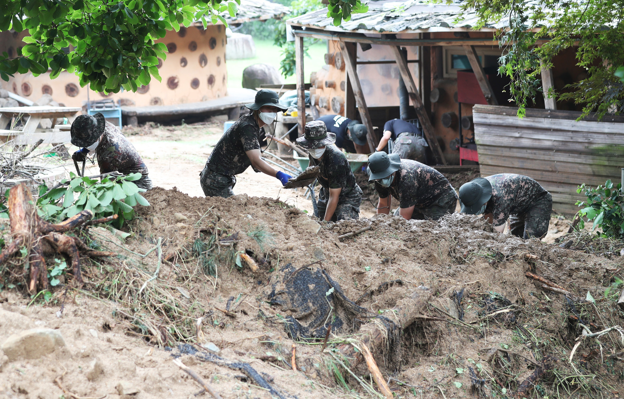 Military service members are at work in Anseong, Gyeonggi Province, on Tuesday to clear the mud piled up from heavy downpour that started over the weekend. (Yonhap)