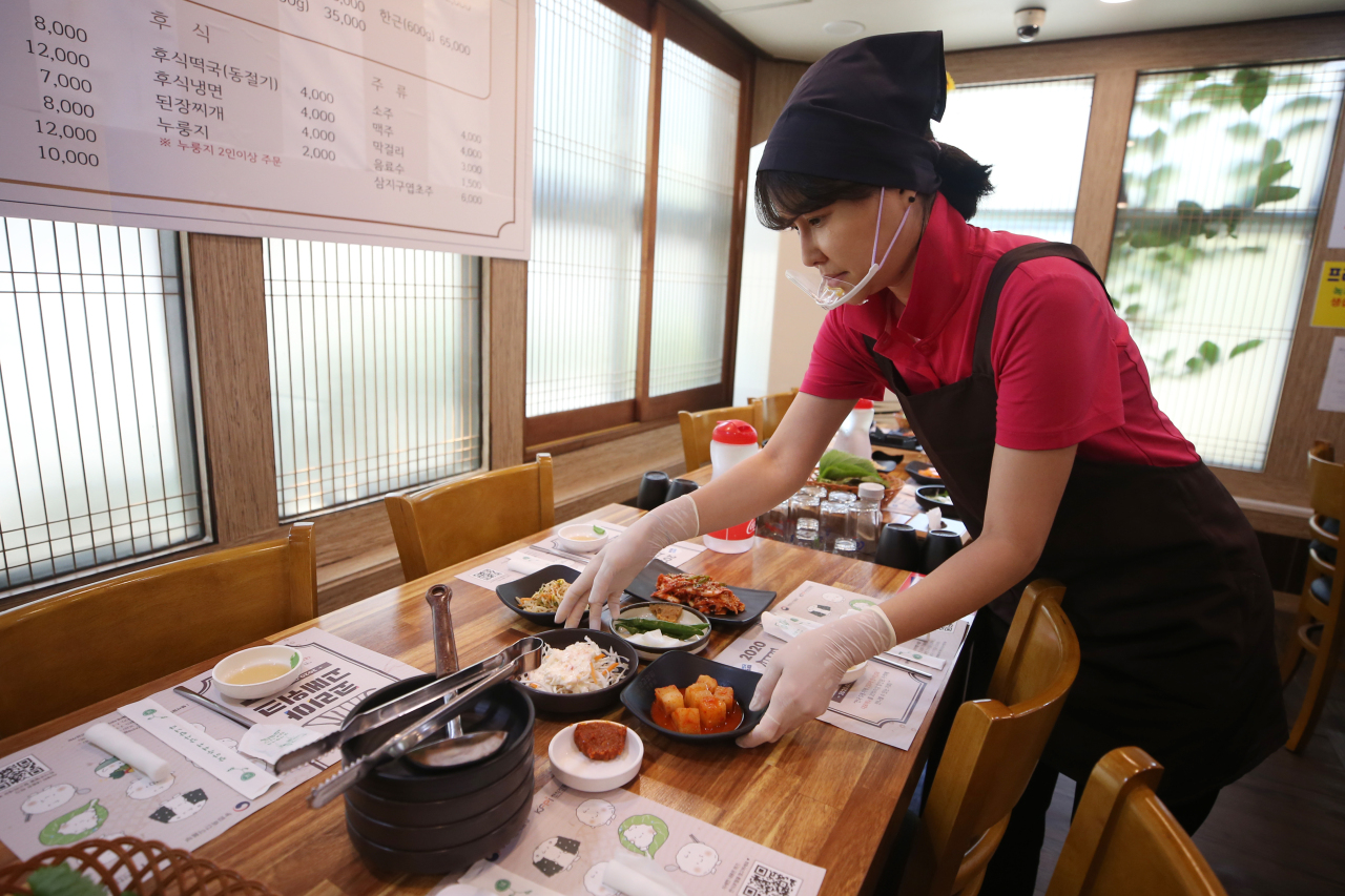 Photo shows a server at a restaurant in Gwangju wearing gloves and a plastic face shield as coronavirus countermeasures. (Yonhap)