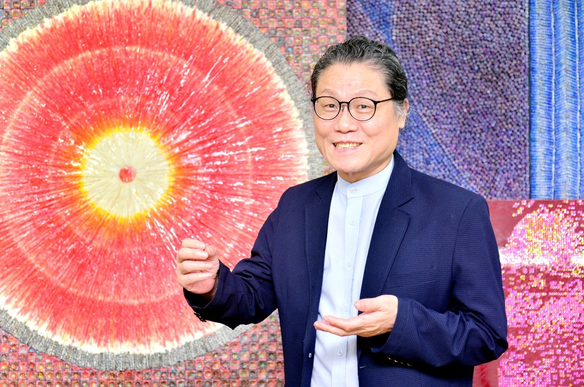 """Emographic artist Huh Hwe-tae poses in front of his new work,""""The Vibration of a Heart,"""" at his studio in central Seoul. (Park Hyun-koo/The Korea Herald)"""