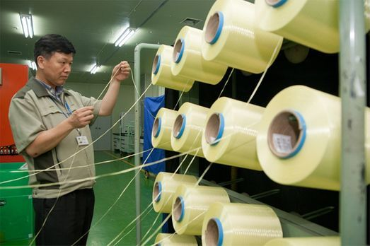 A Kolon Industries official checks the quality of aramid fibers at its plant in Gumi, North Gyeongsang Province.(Kolon Industries)