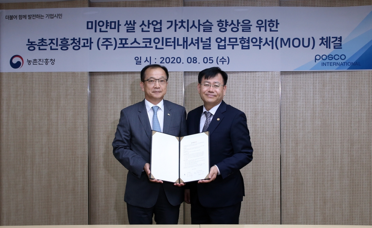 Posco International CEO Joo Si-bo (left) and Rural Development Administration Administrator Kim Kyeong-kyu pose for a photo at a ceremony held on Wednesday in Seoul. (Posco International)