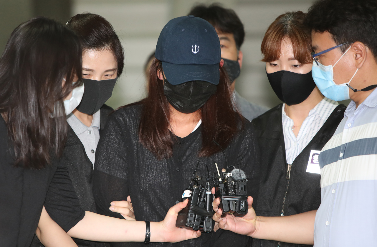 Jang Yun-jung, a former triathlete, is escorted out of a court in the southeastern city of Daegu on Wednesday after a hearing on her arrest warrant for allegedly abusing her teammates, including the late Choi Suk-hyeon. (Yonhap)