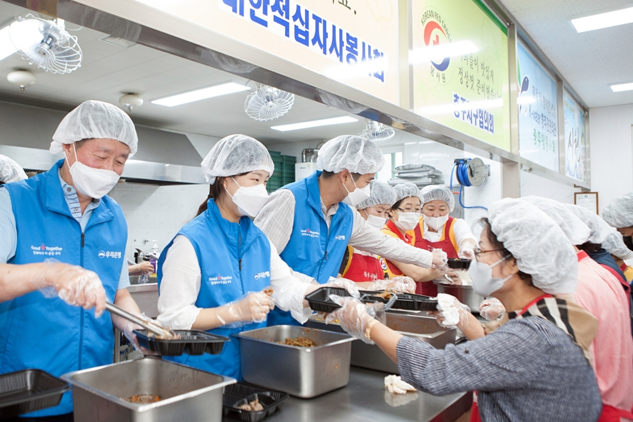Woori Financial Group employees cooperate with Korean Red Cross officials in packing meal boxes for flood victims at a volunteer center in Chungju, North Chungcheong Province on Friday. (Woori Financial Group)