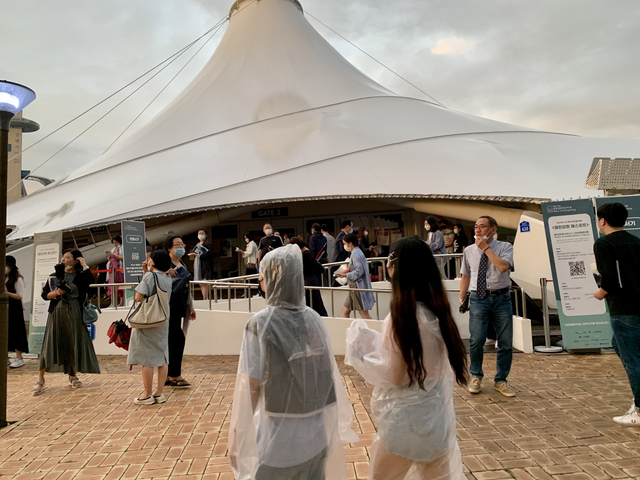 Visitors in raincoats pass by the Alpensia Music Tent in PyeongChang, Gangwon Province, Friday. (Im Eun-byel / The Korea Herald)