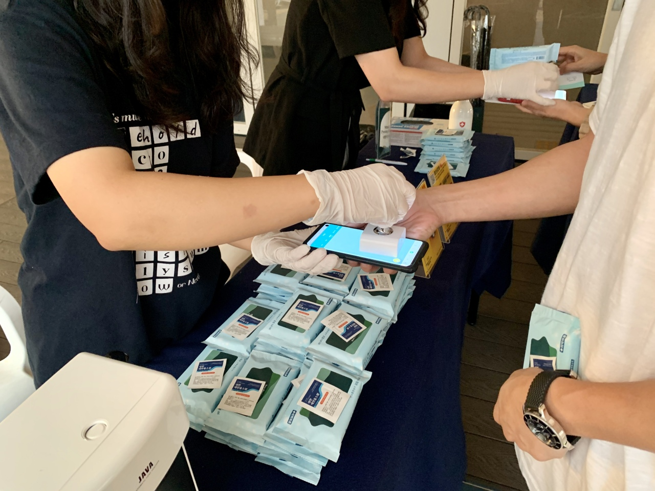 "A staff member gives an ""electronic stamp"" to a festivalgoer using the Clean Gangwon Passport app, after checking his health condition. (Im Eun-byel / The Korea Herald)"