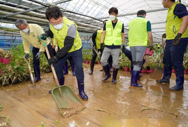 NH NongHyup Chairman Kim Gwang-soo (second from left) volunteers with employees on repairing damaged facilities at a plant farm in Yongin, Gyeonggi Province. (NH NongHyup)