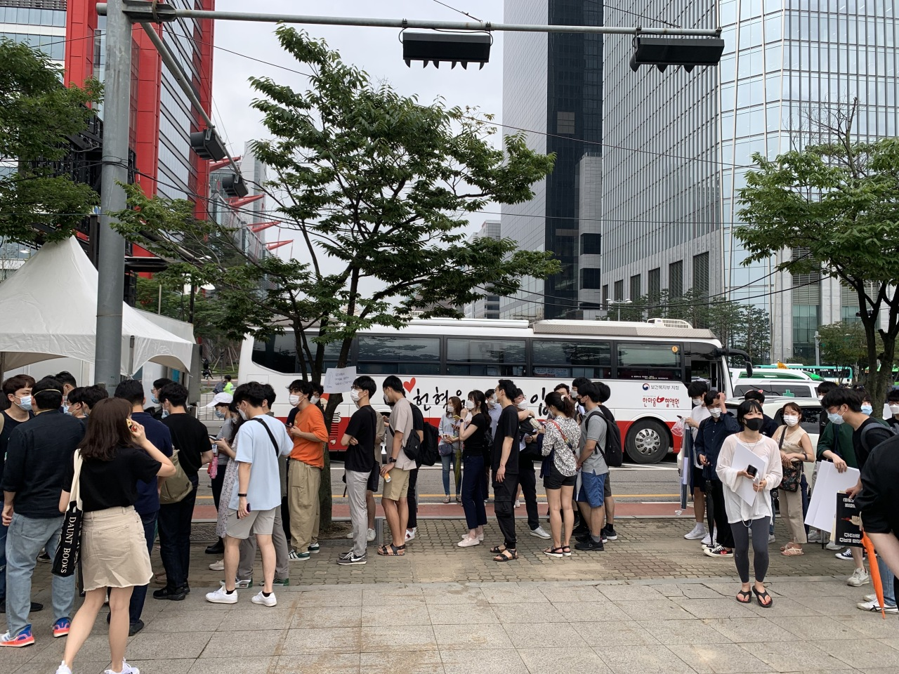 Junior doctors line up to get their symptoms checked before they participate in the march. Behind them is a blood donation vehicle where the young doctors donated blood. (Kim Arin/The Korea Herald)