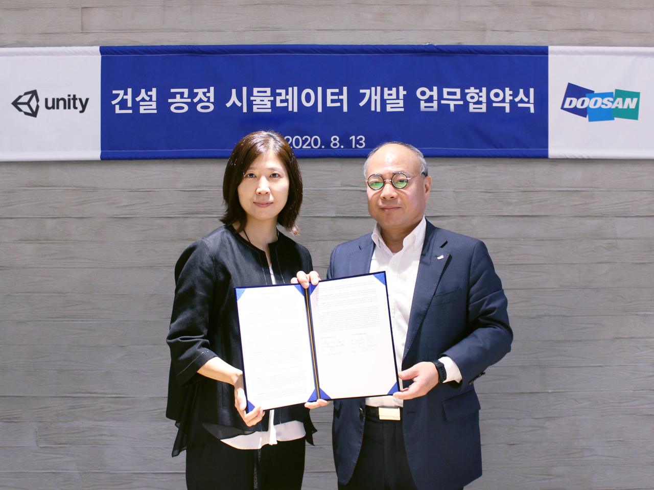 Unity Technologies Korea's Country Manager Kim In-suk (left) and Doosan Infracore Vice President Lee Dong-wook pose for a photo after signing a memorandum of understading to use Unity's game engine for checking the safety of Doosan's construction sites inside virtual reality. (Unity)