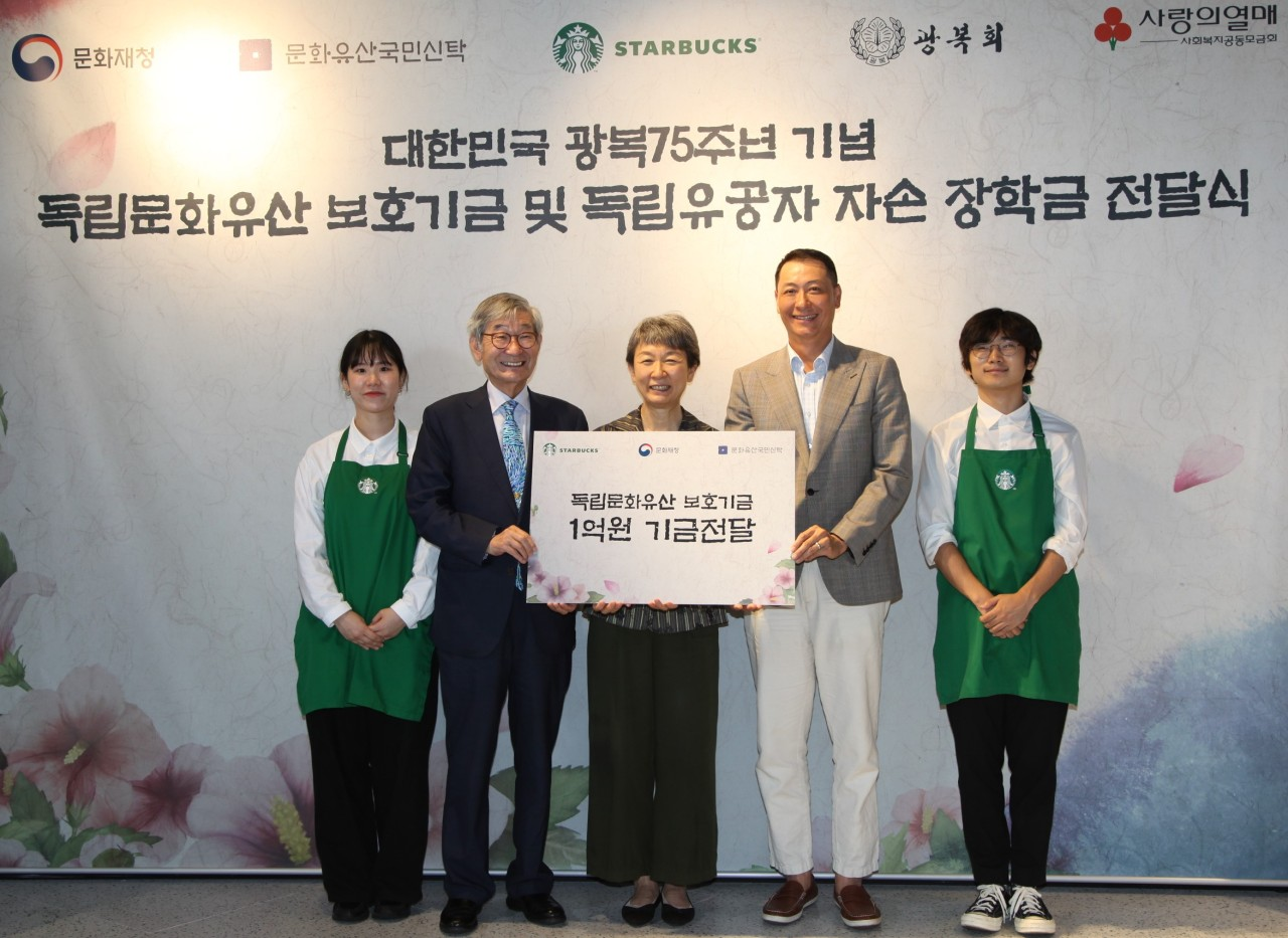 Starbucks Korea Chief Executive Song Ho-seop (second from right) delivers 100 million won to the Cultural Heritage Administration and the National Trust for Cultural Heritage. (Starbucks Korea)
