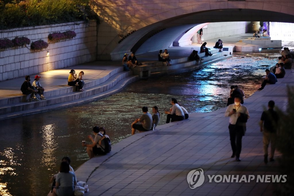 Citizens sit along Cheonggye Stream in central Seoul on the night of June 22, as hot weather continued after the daytime temperature reached the year's high of 35.4 degree Celsius. (Yonhap)