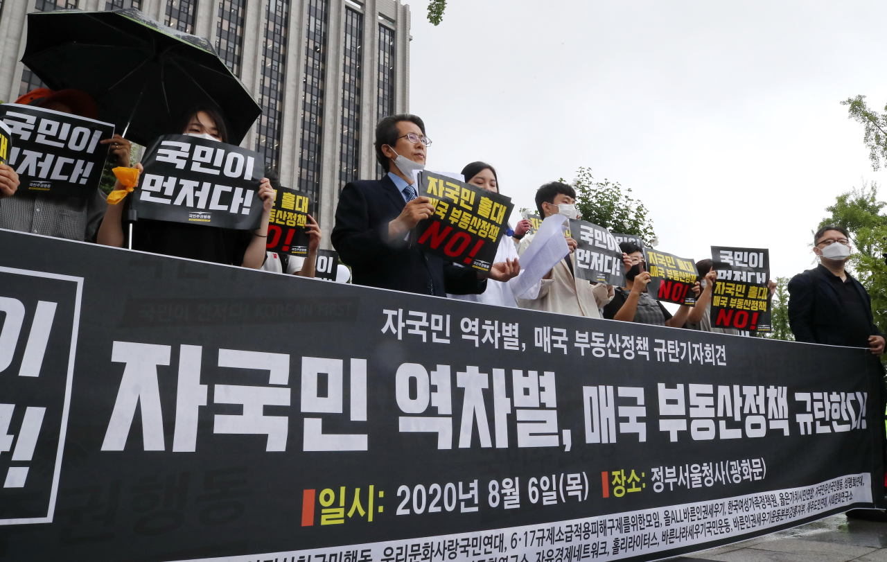 A nongovernmental organization protests the government`s real estate policies outside the government complex in Seoul on Aug. 6. Yonhap