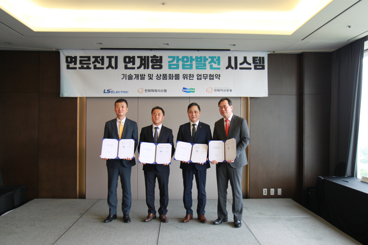 Hanwha Power Systems head of sales Son Young-chang (second from right) and Doosan Fuel Cell Managing Director Lee Seung-jun (third from right) pose for a photo after signing a memorandum of understanding for developing a decompression generation system. (Hanwha Power Systems)