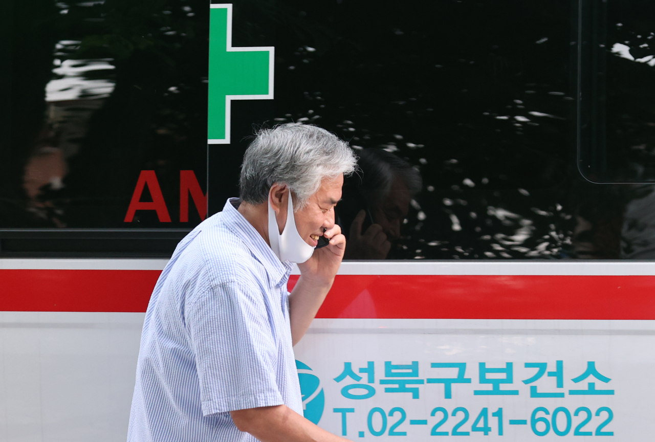 Jun Kwang-hoon is photographed not wearing his mask properly while walking toward an ambulance waiting to take him to a hospital for COVID-19 treatment, near his residence in Seongbuk-gu, Seoul, Monday. (Yonhap)