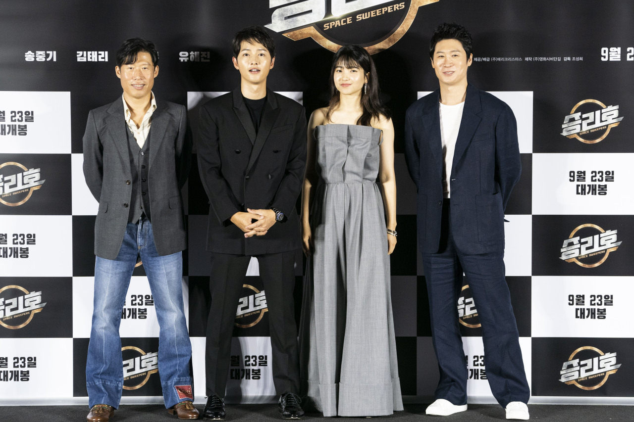 """The cast of the film """"Space Sweepers"""" -- (from left) Yoo Hai-jin, Song Joong-ki, Kim Tae-ri and Jin Seon-kyu -- pose for photos during an online press conference held Tuesday. (Merry Christmas)"""