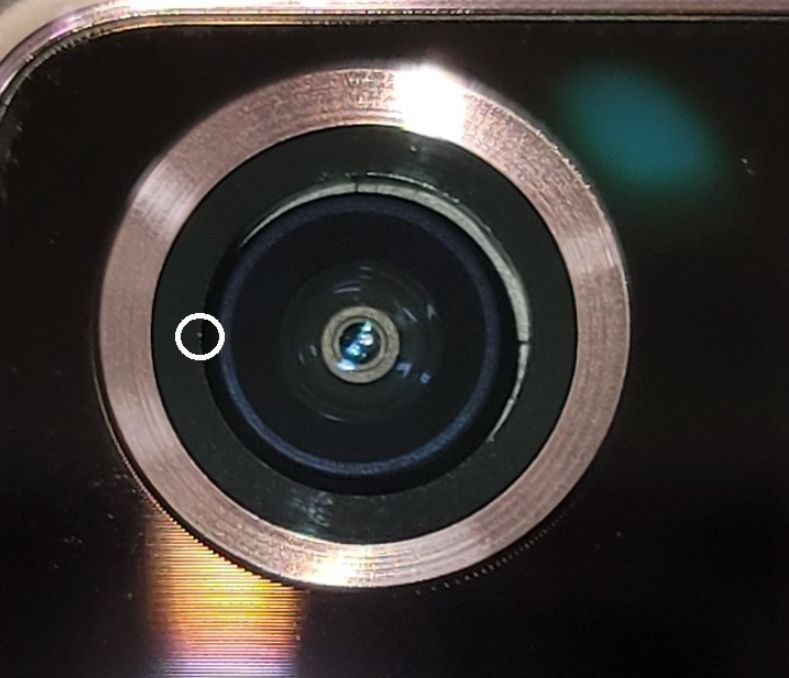 A fine dust particle is inside the camera module of Galaxy Note 20 Ultra smartphone. Also, a lens and the ring surrounding it fit poorly, creating a white gap. (Captured from Samsung Smartphone Community)