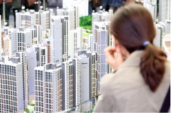 A visitor to an apartment model house in Seoul looks at a miniature of a planned complex. (Yonhap)