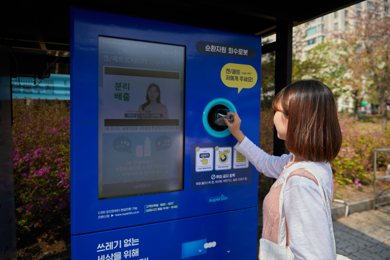 A Seoulite uses Nephron, a reverse vending machine developed by recycling solutions maker Superbin, to recycle plastic bottle in return for financial rewards in Yeouido, Seoul. (Superbin)