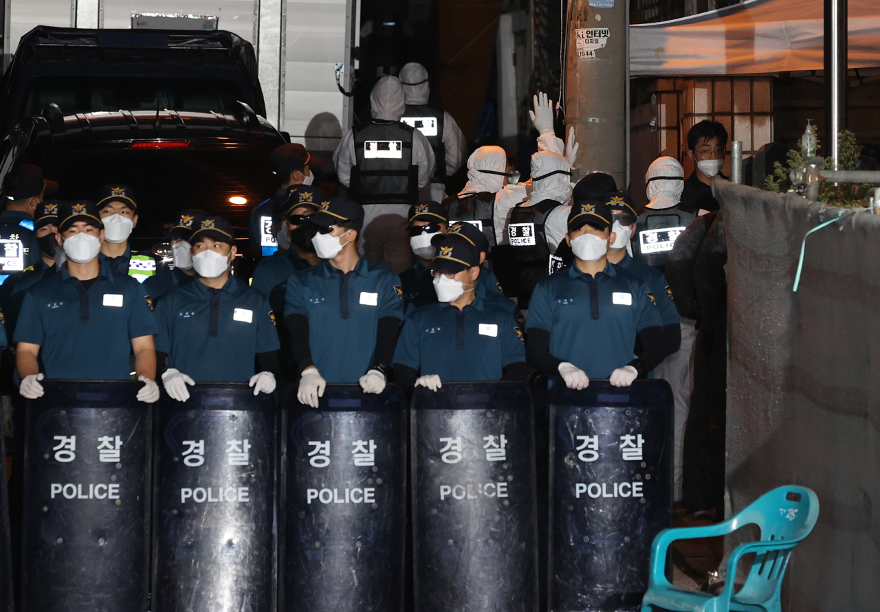 Police officers wearing protective gear enters Sarang Jeil Church in Seoul on Friday for a search and seizure operation. (Yonhap)