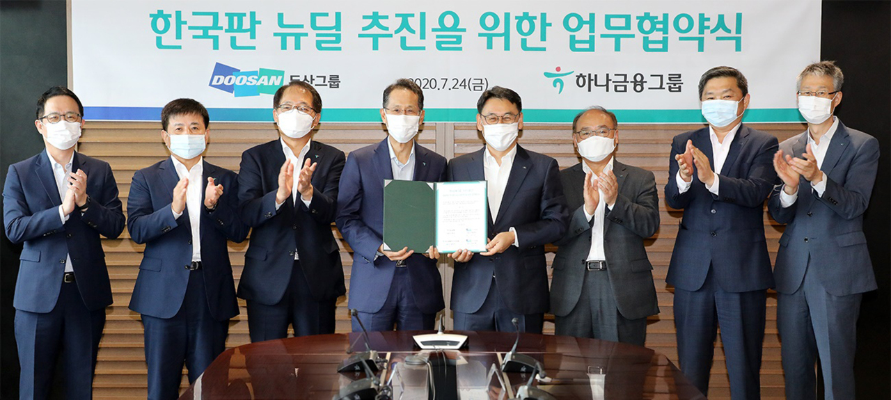 """Hana Bank CEO Ji Sung-kyoo, fourth from left, and Doosan Heavy Industry & Construction COO Jung Yeon-in, fourth from right, take a group photo after signing a memorandum of understanding for cooperation for the """"Korean New Deal,"""" initiative at the lender's headquarters in central Seoul on July 24. (Hana Financial Group)"""
