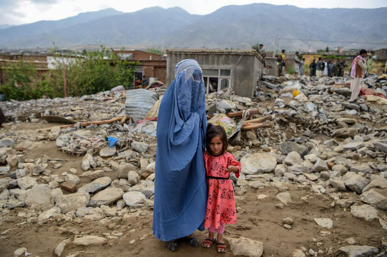 A burqa-clad woman stands near a young girl among households' debris after a flash flood affected the area at Sayrah-e-Hopiyan in Charikar, Parwan province, on Aug. 26, 2020. (AFP)