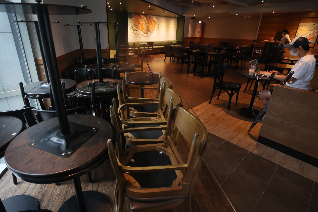 Unused tables and chairs are piled up inside a cafe on Friday. (Yonhap)