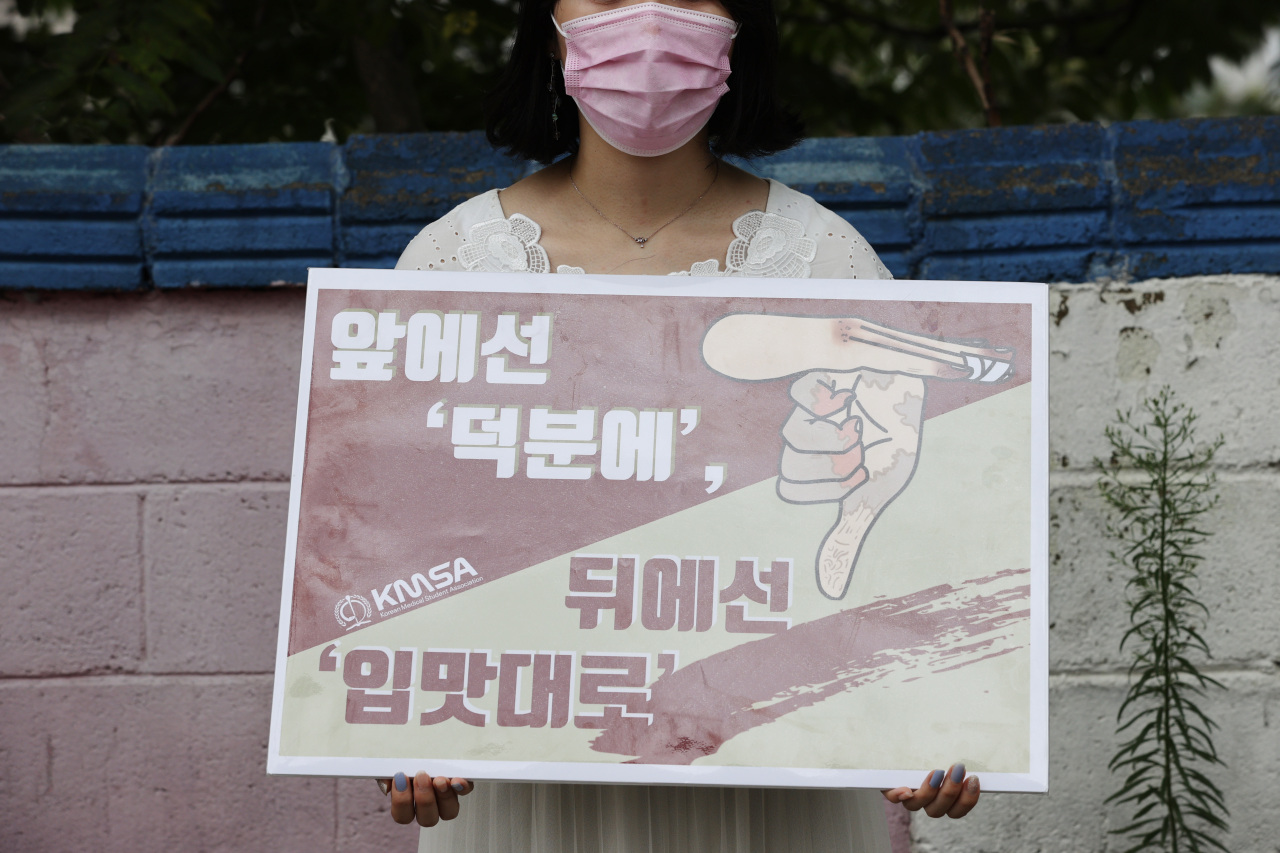 A member of the Korean Medical Student Association stages a single-person rally, opposing the government's policy to increase quotas for medical school admissions across the nation, in Heukseok-dong, Seoul, in August. (Yonhap)