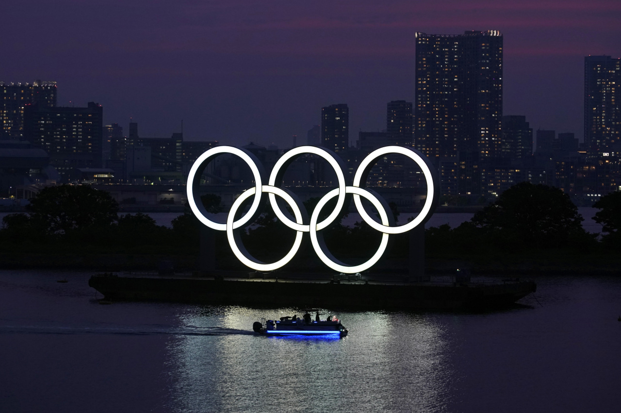 The Olympic rings float in the water at sunset in the Odaiba section in Tokyo, June 3, 2020. (AP-Yonhap)